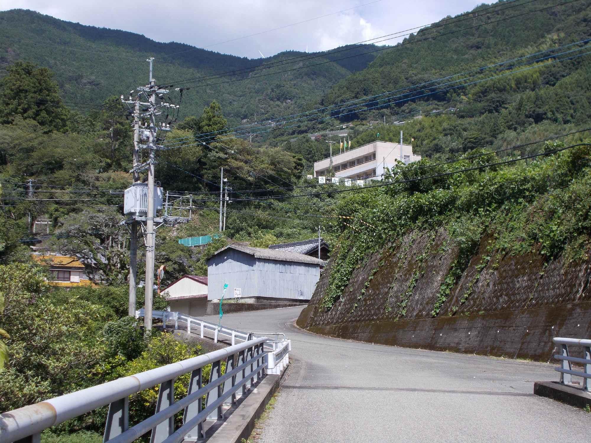施設を県道付近から望む。谷合いの傾斜地にあり、旧校庭も大変狭い
